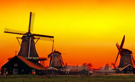 Beautiful sunset in Holland with a view at pasture with wind mills. Zaandam photo