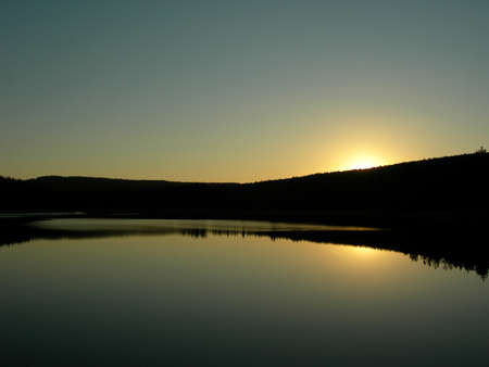 Sun is setting behind forest an is mirroring in the lake photo