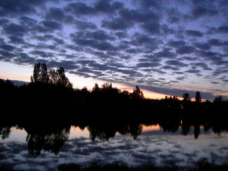 Beautiful sunset with clouds and lake with mirroring village Stock Photo - 15626076