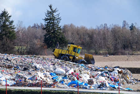 junkyard: Bulldozer is processing waste in the dump