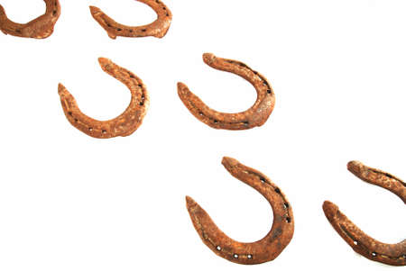 Two rows of old rusty horseshoes on white Stock Photo - 15623976