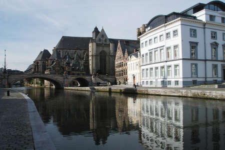 gabled: gabled houses along a canal in Gent, Belgium with reflection on the water and Saint Bravo Cathedral