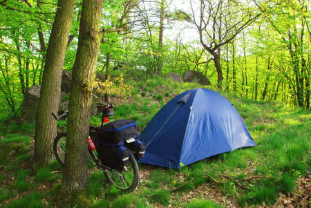 Biker is camping with the tent in green forest photo