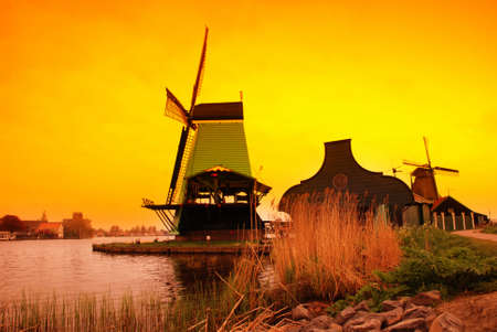 windy energy: Beautiful sunset in Holland with a view at pasture with wind mills. Zaandam Stock Photo