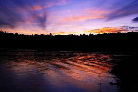 Sun is setting behind forest and is mirroring in the lake photo