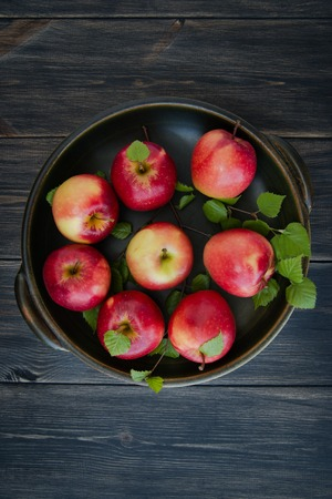 food basket: red apples on wooden table close up Stock Photo