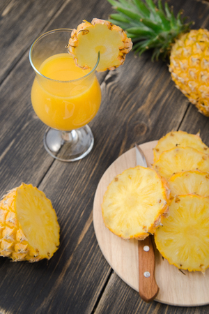 pineapple  glass: pineapple juice in glass on a wooden rustic table