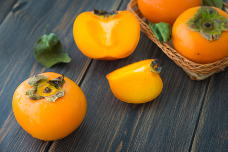 Sliced ripe persimmons with green leaves on dark rustic wooden background closeup