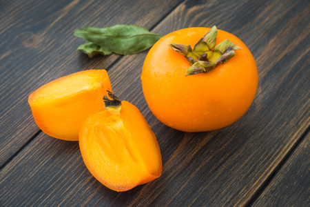 A sweet bright persimmon close-up on dark rustic wooden table Stock Photo
