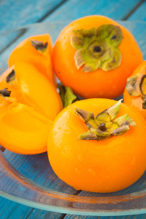 Wet ripe persimmons or date-plum fruits in glass plate on blue rustic wooden background closeup 스톡 콘텐츠
