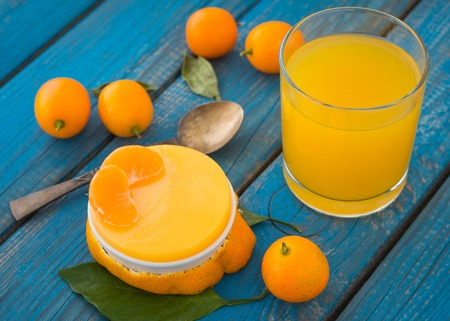 A citrus jelly with a glass of orange juice on blue rustic wooden background closeup