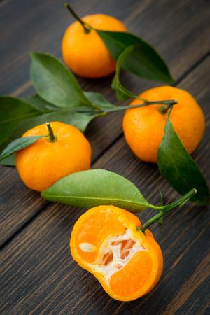 Sliced orange clementine tangerine fruit with green leaf on dark wooden background close-up