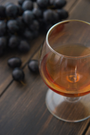 A wineglass of brandy or cognac with a bunch of black grapes on dark wooden rustic background close-up