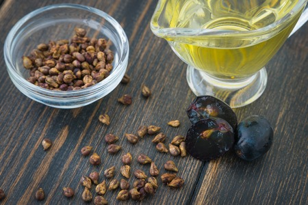 A glass oiler of natural grapeseed oil and grape seeds on black wooden background