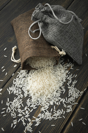 Raw Basmati rice in small jute bags on dark wooden background top view