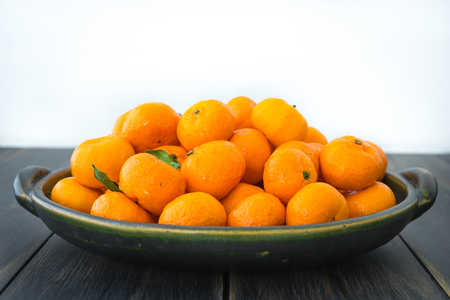 A platter of fresh orange Clementines or Algerian Mandarins on dark wooden table close-up Stock Photo