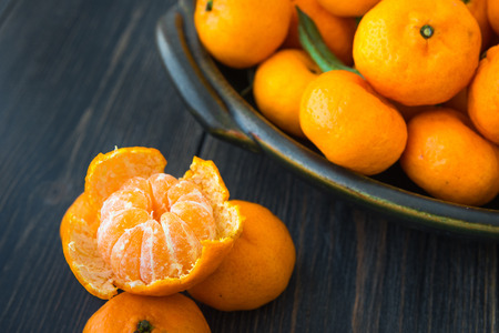 Bright peeled tangerine and a platter of fresh orange Clementines or Algerian Mandarins on dark wooden table close-up