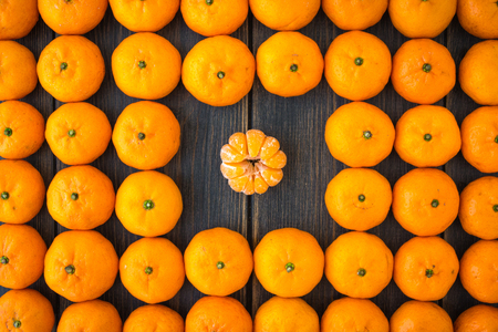 A set of clementines or Algerian mandarins on black wooden background top view