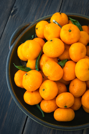 Ripe orange clementines or Algerian Mandarins in dark green porcelain platter on black wooden background top view