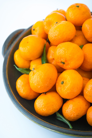 Ripe orange clementines or Algerian Mandarins in dark green porcelain platter isolated close-up