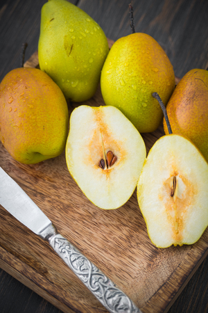 Sliced pears of varying degrees of ripeness in brown craft wooden plate on black rustic wooden table close-up