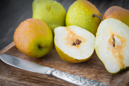 Sliced sweet pears with a silver knife in brown rustic wooden plate close-up