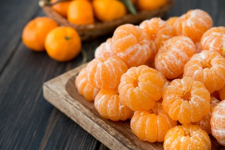 A craft wooden platter of peeled Clementine tangerines on dark wooden background close-up