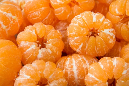 A group of peeled orange Clementine tangerines texture pattern background, top view close-up Фото со стока