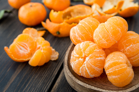 Peeled Clementine tangerines in a craft wooden plate on black wooden background close-up