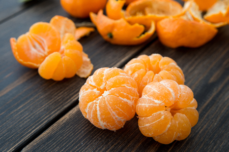 Peeled small tangerines or clementines on dark wooden background close-up