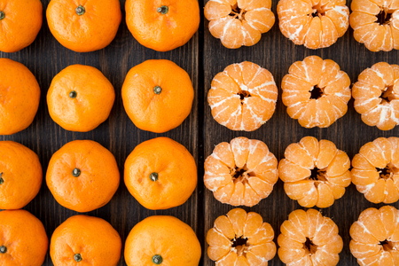 Variety of small tangerines or clementines on dark wooden background top view