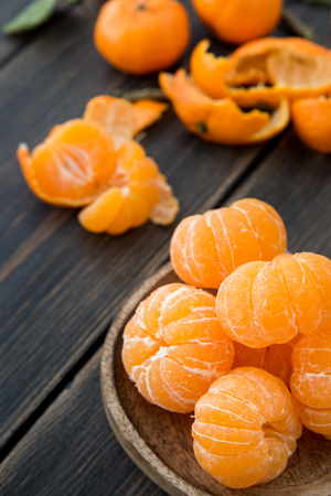 Peeled small tangerines or clementines in a craft wooden plate on dark wooden background close-up Stock Photo