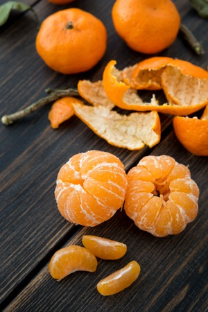 Peeled small Clementine tangerine slices on dark wooden table close-up