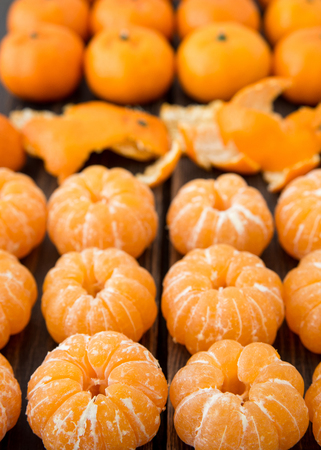 Variety of small tangerines or clementines on black wooden background close-up
