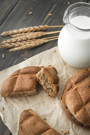 Slices of Finnish rye flatbread scones with a jug of milk on dark rustic wooden table close-up