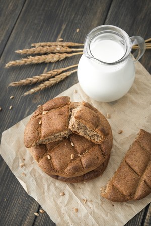 Fresh milk in a glass jug with crumbled rye bread scones on dark rustic wooden background close-up