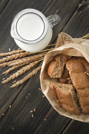 Crumbled rye round flatbread scones with a jug of milk on black rustic wooden background top view