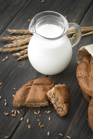 Slices of black rye bread with fresh milk in a glass jug on dark wooden table close-up Фото со стока