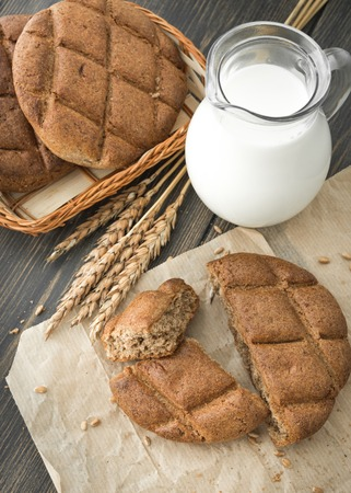 Diet rye flatbreads or griddle cakes with a pitcher of fresh milk on black rustic wooden background close-up