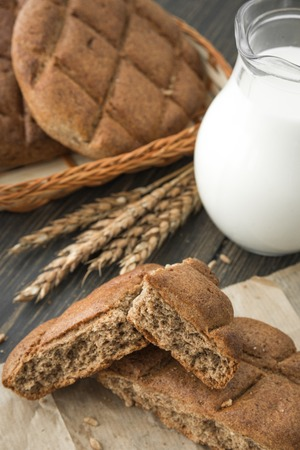 Brown rye breadcrumbs and a glass decanter of milk on dark wooden background close-up