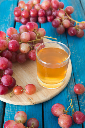 A glass of fresh grape juice and red grapes on a blue wooden rustic background.