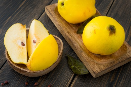 Ripe yellow quince or queen apple fruits and sliced quince lobules with seeds in craft wooden plates on black rustic wooden table close-up Фото со стока
