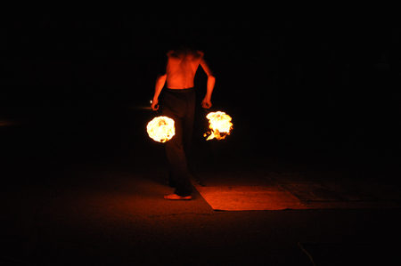 Fire show performance at night, flames in the dark Фото со стока