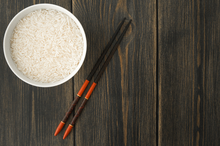Raw Basmati rice in white porcelain bowl and food chopsticks on black wooden background top view Фото со стока