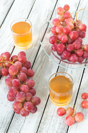 Two glasses of fresh grape juice and red grapes on a white wooden rustic table.
