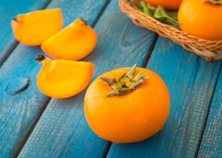 A delicious ripe persimmon or date-plum fruit on blue rustic wooden texture close-up