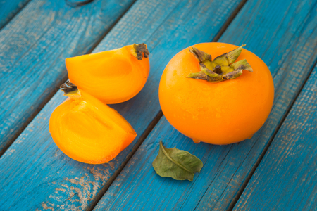 Delicious ripe persimmons with green leaves on blue rustic wooden background close-up