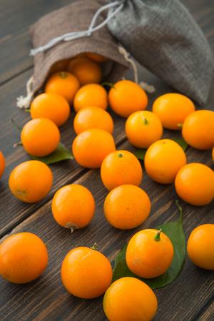 Cumquats, kinkans or fortunella orange fruits with fabric bags on dark rustic wooden background closeup Фото со стока