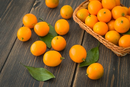 A wicker basket of cumquats or wild orange fruits with green leaves on dark rustic wooden background closeup