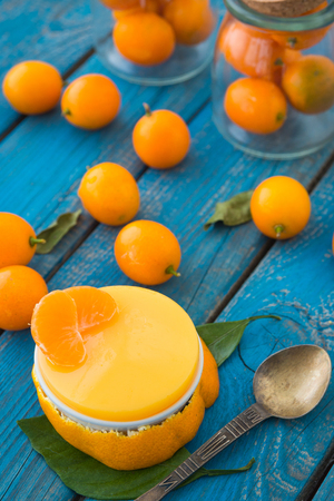 A delicious dessert citrus jelly with cumquats or kumquats on blue rustic wooden table